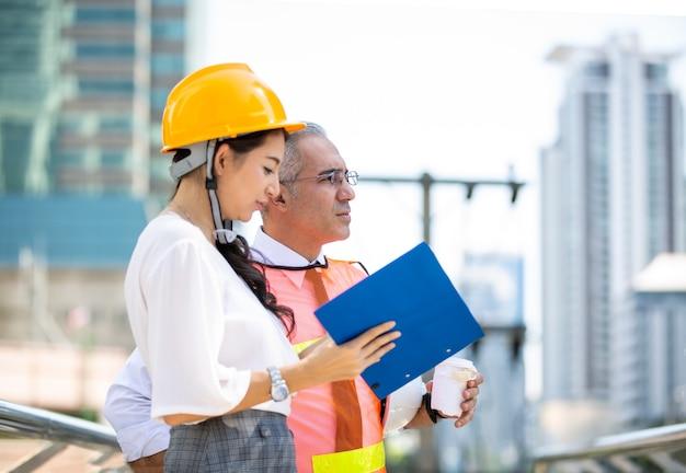 Ingénieurs en construction travaillant et vérifiant un nouveau projet sur un chantier de construction