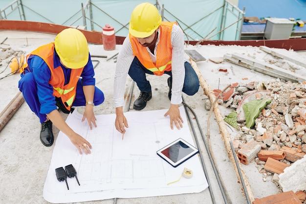 Ingénieurs discutant des détails du plan directeur