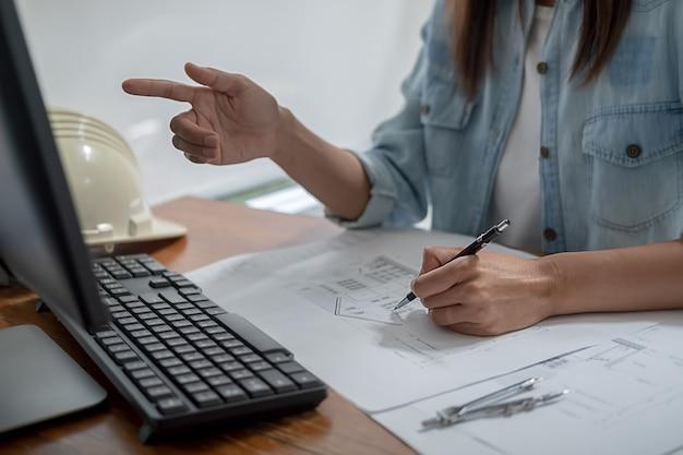 Les ingénieurs discutent d'un plan lors de la vérification d'informations sur une tablette dans un bureau.
