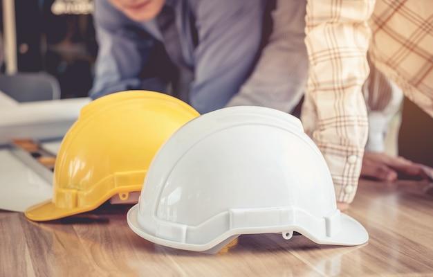 Les ingénieurs du chapeau blanc et jaune sur une table en bois.
