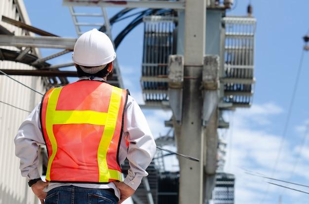 Ingénieurs électriciens debout sur le chantier avec un fond de transformateur sur un poteau électrique