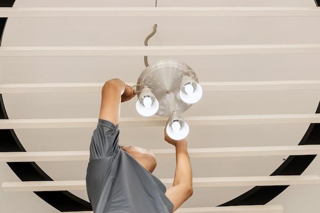 Les ingénieurs électriciens installent des plafonniers dans le couloir.