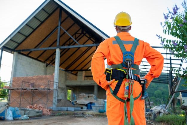 Ingénieurs électriciens portant un harnais de sécurité et une ligne de sécurité debout sur le chantier de construction