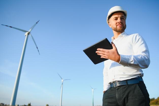 Ingénieurs électriciens travaillant à la station de production d'énergie éolienne avec ordinateur portable