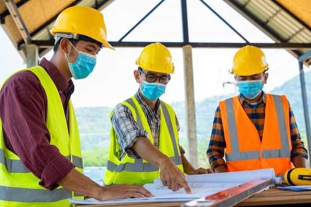 Les ingénieurs de l'équipe et les constructeurs portant des masques de protection pour prévenir la poussière et la maladie de la convection 19 lors de l'inspection sur le chantier, le coronavirus est devenu une urgence mondiale.