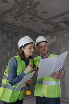 Ingénieurs féminins et masculins dans des casques blancs et des gilets de sécurité jaunes à la construction