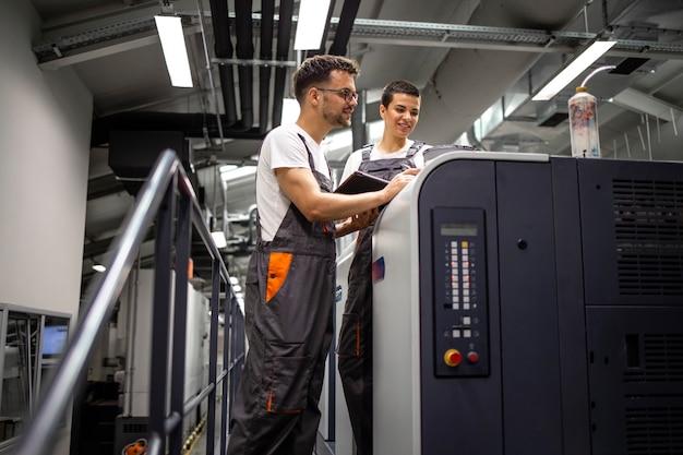 Ingénieurs graphiques vérifiant la machine d'impression pendant le processus d'impression.