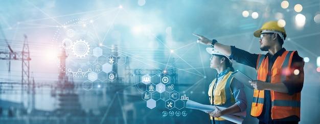 Ingénieurs industriels utilisant une tablette et des plans pour vérifier et analyser les données de la centrale électrique