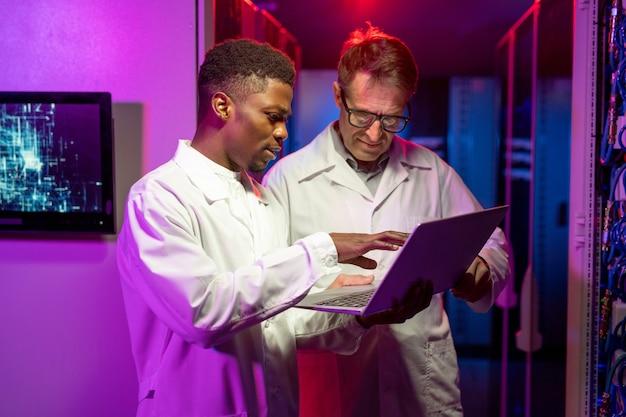 Ingénieurs informatiques multiethniques analysant des données sur un ordinateur portable
