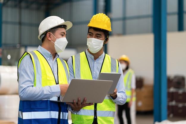 Les ingénieurs masculins asiatiques portent un masque protège le coronavirus protègent le coronavirus tiennent un ordinateur portable parlant au travail