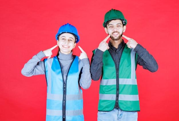 Ingénieurs masculins et féminins avec des casques pointés sur eux-mêmes.
