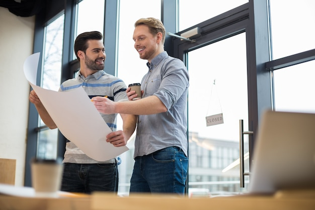 Des ingénieurs masculins intelligents et gais debout ensemble et discutant de leur projet tout en travaillant ensemble