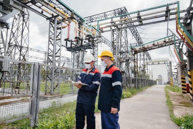 Des ingénieurs masqués inspectent une sous-station électrique
