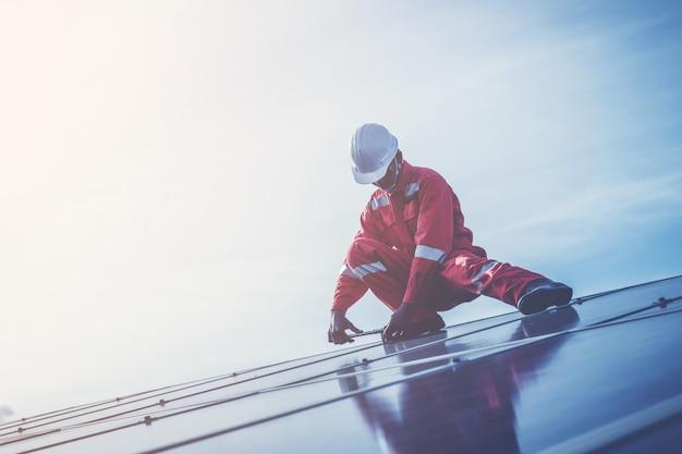 Ingénieurs opérant et vérifiant la puissance de production d'une centrale solaire sur un toit solaire