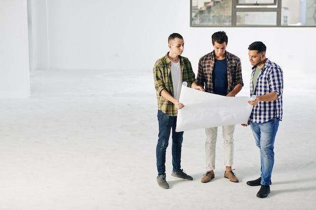 Ingénieurs avec papier de plan de construction