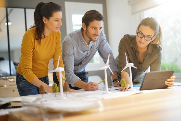 Des ingénieurs de parcs éoliens attrayants examinent les emplacements des turbines