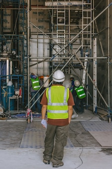 Les ingénieurs portent des vêtements blancs pour casque tiennent le plan sur un chantier de construction avec un échafaudage