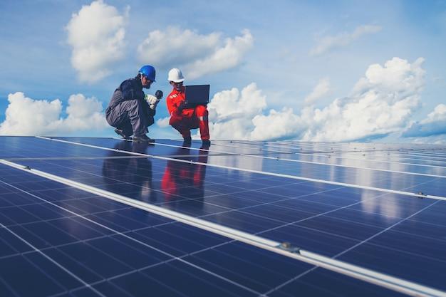 Ingénieurs qui exploitent et vérifient la puissance de production d'une centrale solaire sur un toit solaire