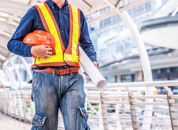 Les ingénieurs se préparent au travail avec orange helmet et blue print.