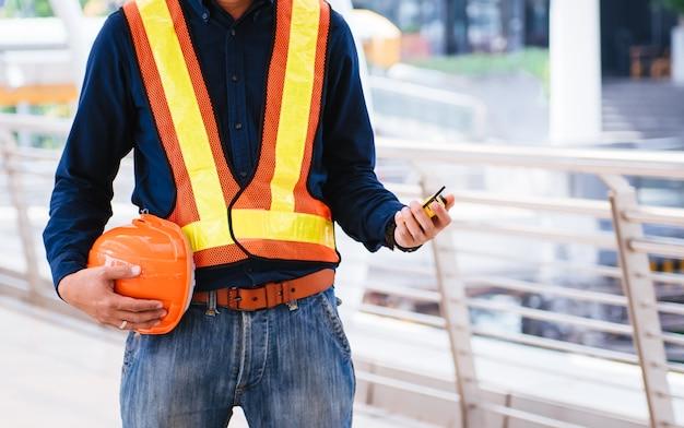 Les ingénieurs se préparent au travail avec orange helmet et le ruban à mesurer.