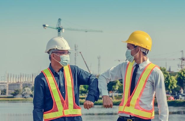 Ingénieurs se saluant en touchant les coudes, deux hommes d'affaires se serrent la main sans contact en plein air sur la construction du site