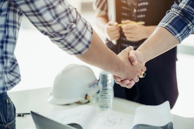 Les ingénieurs se serrent la main avec la secrétaire sur le côté.