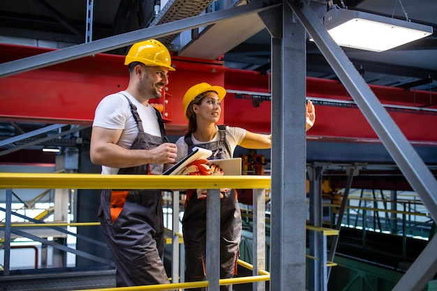 Ingénieurs d'usine en équipement de protection debout dans le hall de production et partageant des idées
