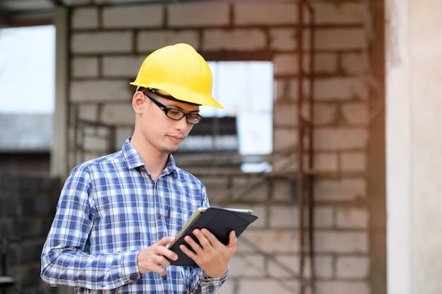 Les ingénieurs utilisent des tablettes pour vérifier la construction. ingénieur portant des lunettes en regardant la tablette.