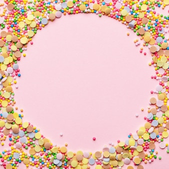 Ingrédient de pâtisserie de gâteau sucré. saupoudrer de sucre en forme de cercle. cadre rond avec garniture de pâtisserie. conception vide au centre. isolé sur fond rose. concept de vacances et d'anniversaire.