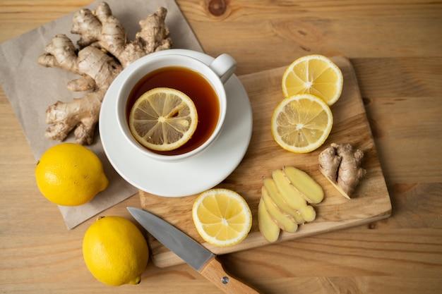 Ingrédient pour réchauffer le thé. racines de gingembre entières et tranchées, citron sur vue de dessus de mur blanc.