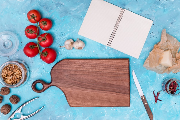 Ingrédient sain et ustensile de cuisine avec journal vierge ouvert sur fond texturé bleu