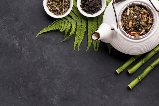 Ingrédient de thé séché et bâton de bambou avec des feuilles de fougère sur une surface noire