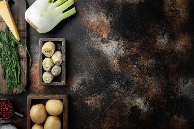 Ingrédients al forno de pomme de terre et d'artichaut, sur le vieux fond rustique, vue supérieure avec l'espace pour le texte
