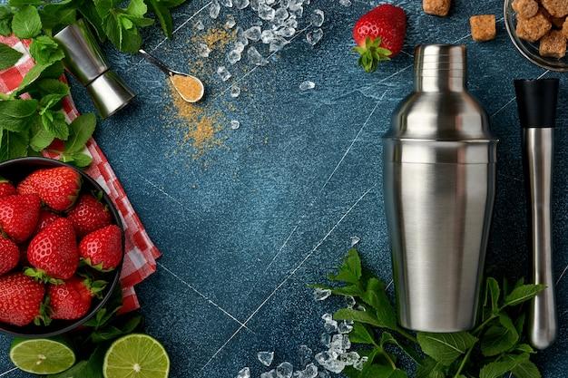 Ingrédients alimentaires frais pour faire de la limonade, de l'eau de désintoxication infusée ou un cocktail. fraises, citron vert, menthe, basilic, sucre de canne, glaçons et shaker sur fond bleu foncé en pierre ou en béton. vue de dessus.