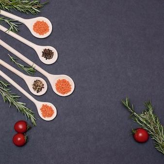 Ingrédients alimentaires italiens encore la vie de la cuisson des pâtes sur une vue de dessus de fond noir. cuillères en bois avec des épices. cadre de produits et légumes.