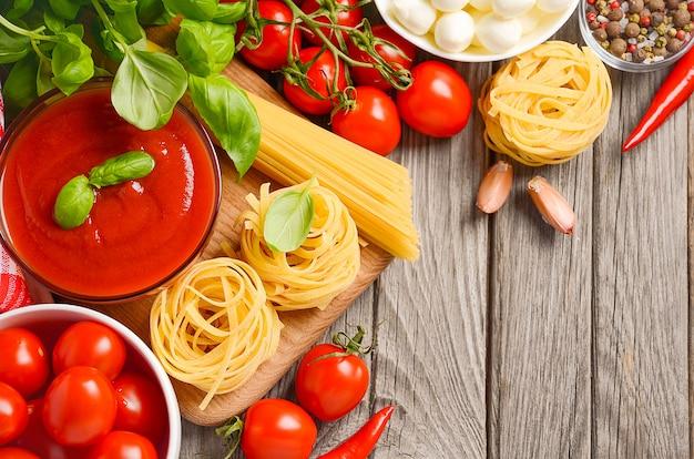 Ingrédients alimentaires italiens mozzarella, tomates, basilic et huile d'olive sur fond en bois rustique.