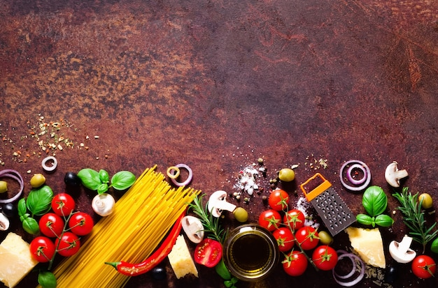 Ingrédients alimentaires pour les pâtes italiennes, spaghettis sur fond brun foncé.