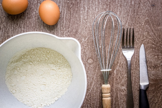 Ingrédients alimentaires et ustensiles de cuisine pour cuisiner sur fond de bois