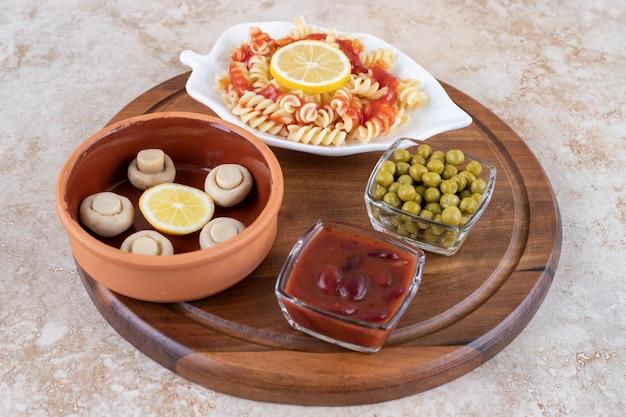 Ingrédients de l'apéritif avec un plateau de macaronis sur une surface en marbre.