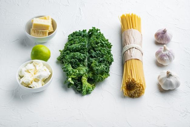 Ingrédients de base pour la cuisson des pâtes, feuille verte, ricotta, parmesan, sur blanc