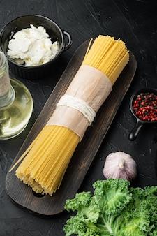 Ingrédients de base pour la cuisson des pâtes, feuille verte, ricotta, parmesan, sur fond noir