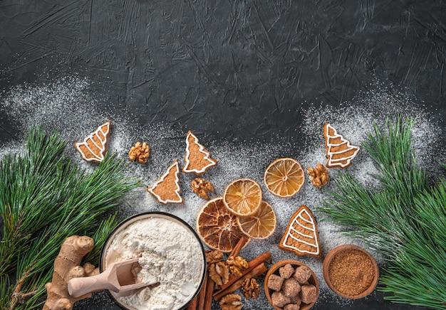 Ingrédients de biscuits au gingembre et branches de pin sur fond noir
