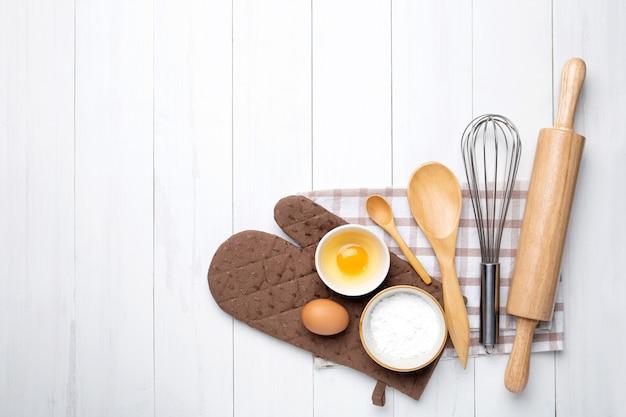 Ingrédients de boulangerie. épis de blé et bol de farine, oeuf, rouleau à pâtisserie, fouet à oeuf sur blanc