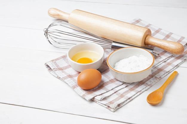 Ingrédients de boulangerie. épis de blé et bol de farine, oeuf, rouleau à pâtisserie, fouet à oeuf, gant de four sur blanc