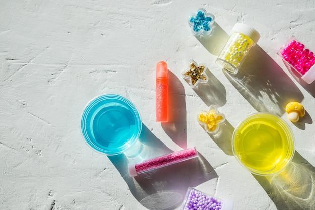 Ingrédients, bouteilles, pots pour fabriquer un jouet pour enfants populaire à partir de colle. slime tendance gélatineux avec des balles pour le divertissement et les loisirs dans des boîtes rondes. pâte à modeler d'argile légère, créativité des enfants