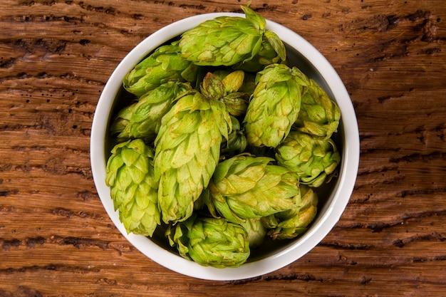 Ingrédients de brassage de bière cônes de houblon dans un bol blanc sur fond de bois. concept de brasserie de bière.