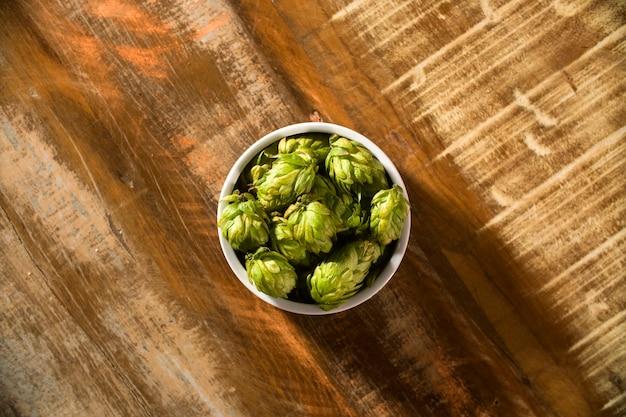 Ingrédients de brassage de bière cônes de houblon dans un bol en bois et épis de blé sur fond en bois. concept de brasserie de bière.