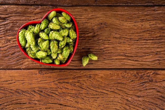 Ingrédients de brassage de bière cônes de houblon dans un bol coeur rouge sur fond de bois. concept de brasserie de bière.