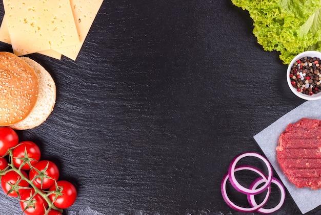 Les ingrédients bruts pour le hamburger fait maison sur fond d'ardoise noire vue de dessus à plat avec espace de copie pour le texte
