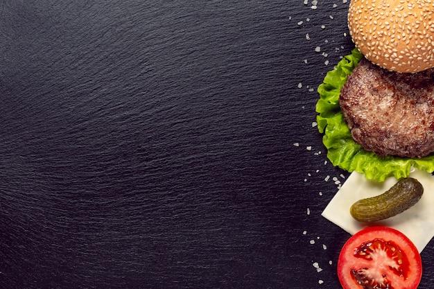 Ingrédients de burger vue de dessus sur fond noir